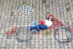 Little boy having fun with race car picture drawing with chalk Stock Photos