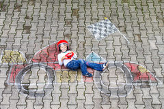 Little boy having fun with race car picture drawing with chalk Royalty Free Stock Image