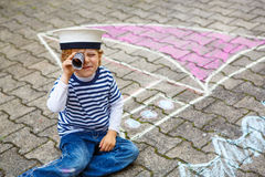 Little boy having fun with ship picture drawing with chalk Royalty Free Stock Images