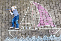 Little boy having fun with ship picture drawing with chalk Royalty Free Stock Photos