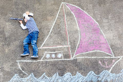 Little boy having fun with ship picture drawing with chalk Stock Photos