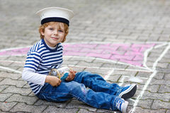 Little boy having fun with ship picture drawing with chalk Royalty Free Stock Photo