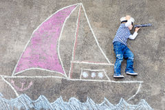 Little boy having fun with ship picture drawing Royalty Free Stock Photography
