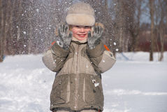 Little boy having fun in the snow. The boy of 3 years laughs, plays in winter day Royalty Free Stock Photography