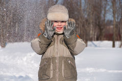 Little boy having fun in the snow. The boy of 3 years laughs, plays in winter day Royalty Free Stock Photos