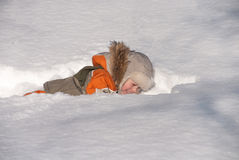 Little boy having fun in the snow. The boy of 3 years laughs, plays in winter day Royalty Free Stock Image