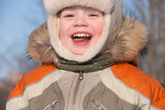Little boy having fun in the snow. The boy of 3 years laughs, plays in winter day Stock Image