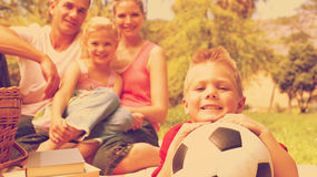 Little boy having fun with a soccer ball. With his family smiling Stock Photography