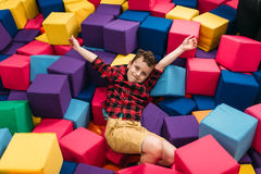 Little boy having fun with soft colorful cubes Stock Photos