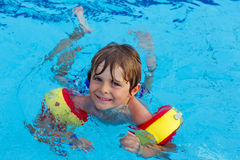 Little boy having fun in an swimming pool Stock Images