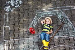 Little boy having fun with tractor picture drawing with chalk Stock Images