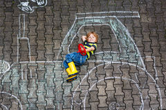 Little boy having fun with tractor picture drawing with chalk Royalty Free Stock Photos