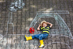 Little boy having fun with tractor picture drawing with chalk Royalty Free Stock Photo