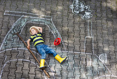 Little boy having fun with tractor picture drawing with chalk Royalty Free Stock Image