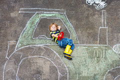 Little boy having fun with tractor picture drawing with chalk royalty free stock images