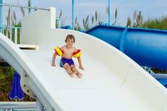Little boy having fun on waterslide pool Royalty Free Stock Photos