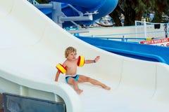 Little boy having fun on waterslide pool Stock Photo