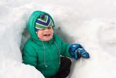 Little boy having fun in winter snow Stock Photos