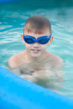 The little boy having good time in the swimming pool. The close up portrait of The little boy in the swimming glasses having good time in the swimming pool Royalty Free Stock Photo