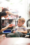 Little boy having a hair cut in a salon Stock Photos