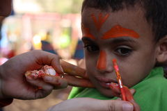 Little boy having his face painted Kids having fun playing Royalty Free Stock Images