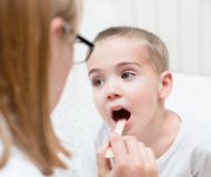 Little boy having his throat examined by health professional Royalty Free Stock Photos