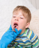Little boy having his throat examined by health professional Royalty Free Stock Image