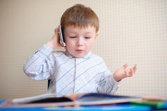 Little Boy Having a Serious Phone Call at desk Royalty Free Stock Photos