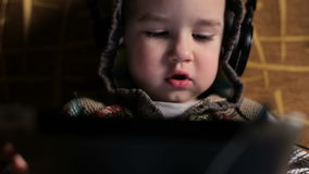 Little boy with headphones browse tablet pc stock video footage
