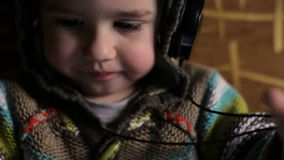 Little boy with headphones browse tablet pc stock footage