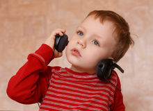 Little boy with headphones at home Stock Images
