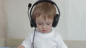 Little boy with headphones shakes his head and waves his arms. Little boy with headphones listening to music, shaking his head and waving his hands stock footage