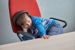 Little boy with headphones sitting at computer in office Stock Images