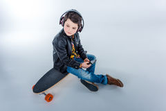 Little boy in headphones sitting on skateboard and looking away Royalty Free Stock Photography