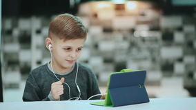 Little boy in headphones is using a digital tablet, sitting at home listening to music stock video footage
