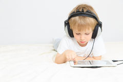 Little boy with headset using touch pad Royalty Free Stock Photos