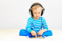 Little boy with headset using touch pad Royalty Free Stock Images