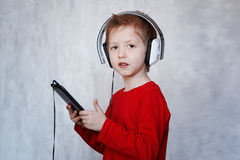 Little boy with headset using touch pad, listening to music with Royalty Free Stock Image