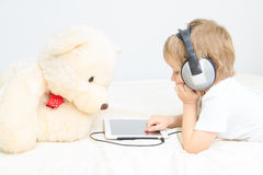 Little boy with headset using touch pad Royalty Free Stock Image