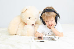 Little boy with headset using touch pad Stock Images