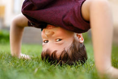 Little boy headstand in grass and laughing Royalty Free Stock Image