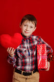 Little boy with a heart of toy and gift box Stock Image
