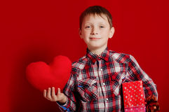 Little boy with a heart of toy and gift box Royalty Free Stock Images