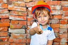 Little boy in helmet. Little boy in the construction helmet against the bricks Stock Photography