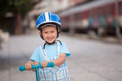 Little boy with helmet, playing with his scooter outdoor Stock Photos