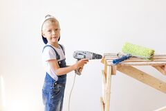 Little boy in a helmet plays in the builder with tools. isolated over white