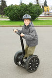 Little boy in helmet ride on segway. Near friendship fountain in Moscow, Russia, side, full body stock photos