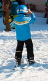 Little boy with helmet after skiing on a sunny day royalty free stock photo