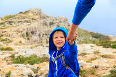Little boy helped by parent on hiking in mountains Stock Photos