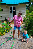 Little boy helping grandmother water flowers Stock Photo